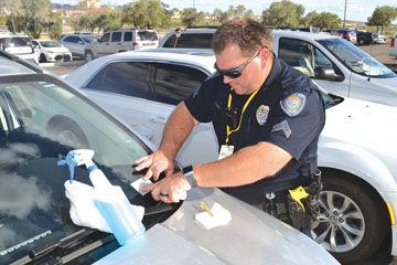 Bullhead City police Cpl. Sean Watson presses a decal onto a windshield Thursday afternoon during a vehicle theft prevention and awareness event. Drivers could get the Vehicle Identification Numbers of their cars etched into all the glass, which reduces i